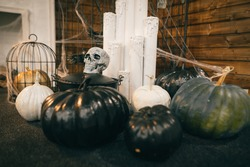 Halloween decorations are on the floor. Pumpkins with a skull and candles decorate the interior for Halloween. Background