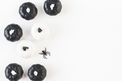 Halloween decorations. Decorative black and white pumpkins on white background. Halloween concept. Flat lay, top view, copy space