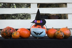 Halloween decorations in new reality of COVID-19 pandemic.  row of pumpkins, one of which has  witch's hat and medical mask with  painted scary smile. Street decor