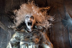 Halloween decorations in the form of a dead woman. Scary woman with her mouth open and spiders on her face