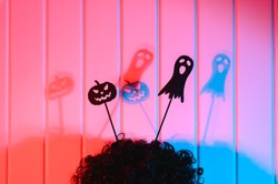 Halloween decorations. Scary black paper dolls of pumpkin and ghost on a wig in the form of horns on the background of a wooden wall. Neon lighting. Close-up.