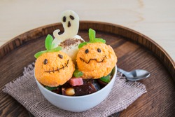 Halloween dessert in a white cup. It consists of ice cream in the form of a ghost pumpkin and a  chocolate white ghost.  Creative food for the holiday and good mood.