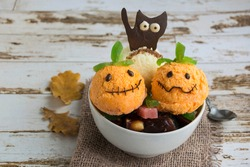 Halloween dessert in a white cup. It consists of ice cream in the form of ghost pumpkins and chocolate black cat. Creative food for the holiday and a good mood.