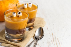 Halloween dessert with cookies, chocolate mousse, pumpkin smoothies, and the eyes of the marshmallow, copy space