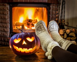 Halloween eve. Female feet in soft wool socks and burning fire in fireplace at the background. Glowing pumpkin stands right on the table in front of the fireplace.