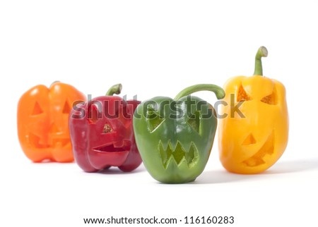 Halloween faces carved into orange, red, yellow and green capsicum vegetables instead of pumpkin forming special jack o lanterns.