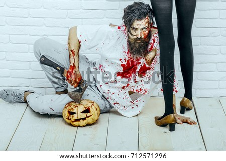 Halloween female legs standing in black pantyhose and shoes. Man sitting with pumpkin and axe on wooden floor. Bearded hipster with red blood splatters. Halloween holiday celebration concept #712571296