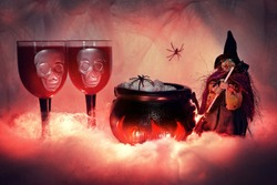Halloween figure of a witch with a broom on a lighted smoky background of cobwebs, standing next to a burning witch's cauldron filled with food and snacks, on which a spider crawls, next to two creepy