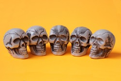 Halloween five skulls, on an orange background, halloween template design, isolated, close up