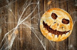 Halloween food. Homemade meat pie with a scary face for Halloween on a wooden table. Copy space.