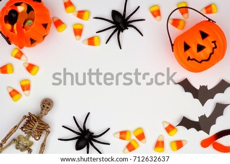 Halloween frame of scattered candy and decor, flat lay over a white background #712632637