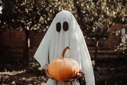 Halloween ghost costume in vintage style. Suit made of sheets. Child in a party costume scares. Trick or treat. Young child dressed as a ghost holding a pumpkin for halloween.