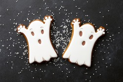 Halloween gingerbread biscuits on black background. Funny white ghosts.