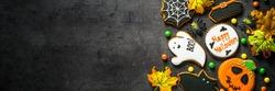 Halloween Gingerbread Cookies - pumpkin, ghosts, witch hat, spiderweb on black background. Top view.