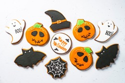Halloween Gingerbread Cookies - pumpkin, ghosts, witch hat, spiderweb on white table. Top view.