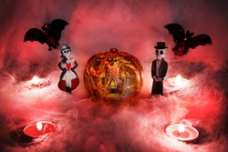 Halloween glowing pumpkin in a reddish smoky background of cobwebs, with figures of a pair of skeletons, a female skeleton in a dress and a figure of a male skeleton in a tailcoat, with candles
