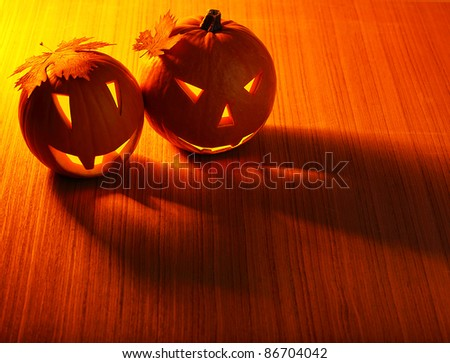 Halloween glowing pumpkins border with leaves over warm wooden background, autumn holiday, traditional party decoration, fun concept