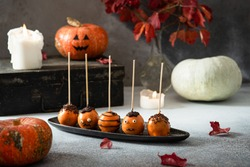 Halloween gourmet cake pops with holiday decor on gray background with pumpkins and candles.