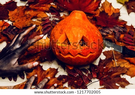 halloween grim, scary zombie hands want to steal a pumpkin. red leaf colors. mystery and mystery #1217702005