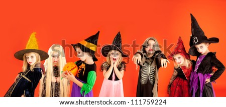 Halloween group of children girls costumes on orange background