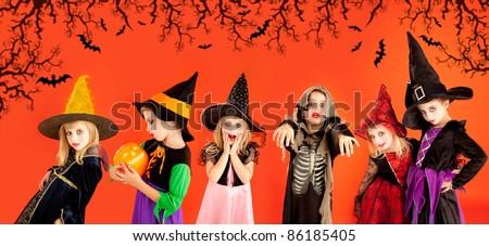 Halloween group of children girls costumes on orange background [Photo Illustration]