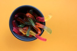 Halloween gummy worms in a bowl. Colorful jelly worms shaped candies. Top view, selective focus