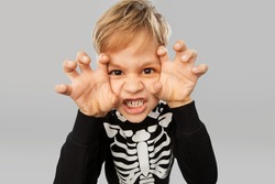 halloween, holiday and childhood concept - boy in black costume with skeleton bones making spooky faces over grey background