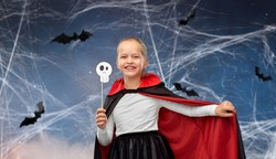 halloween, holiday and childhood concept - girl in dracula costume with black cape holding scull party accessory over night sky with bats and cobweb on background