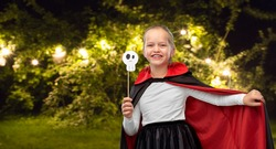 halloween, holiday and childhood concept - girl in dracula costume with black cape holding scull party accessory over lights at night park on background