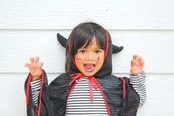 Halloween, holiday and childhood concept. Little kids southeast asian on halloween dressed in a witch costume. funny kids in carnival costumes outdoors.