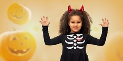 halloween, holiday and childhood concept - smiling african american girl in black costume dress and red devil's horns over jack-o-lanterns on orange background