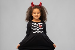 halloween, holiday and childhood concept - smiling african american girl in black costume dress and red devil's horns over grey background