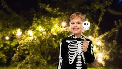 halloween, holiday and childhood concept - smiling boy in black costume of skeleton with scull party accessory making faces over lights at night park on background