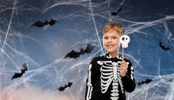 halloween, holiday and childhood concept - smiling boy in black costume of skeleton with scull party accessory making faces over night sky with bats and cobweb on background