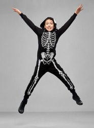 halloween, holiday and childhood concept - smiling boy in black costume with skeleton bones jumping over grey background