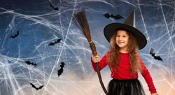 halloween, holiday and childhood concept - smiling girl in costume and witch hat with broom over cobweb and bats flying in starry night sky background