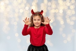 halloween, holiday and childhood concept - smiling girl in party costume with red devil's horns making spooky gestures over festive lights on grey background