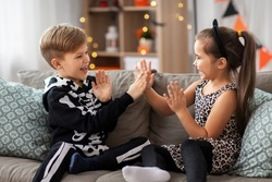 halloween, holiday and childhood concept - smiling little boy and girl in costumes playing clapping game at home