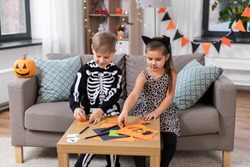 halloween, holiday and childhood concept - smiling little boy and girl in party costumes doing crafts at home