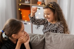 halloween, holiday and childhood concept - smiling little girls in party costumes playing with toy spider at home