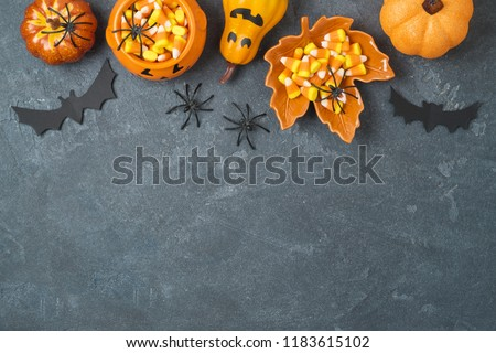 Halloween holiday background with jack o lantern pumpkin, candy corn and decorations on blackboard. View from above. Flat lay #1183615102
