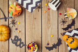 Halloween holiday background with pumpkin and candy. View from above