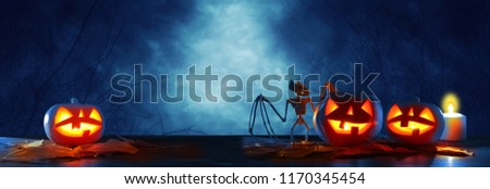 Halloween holiday concept banner. Pumpkins over wooden table at night scary, haunted and misty forest #1170345454