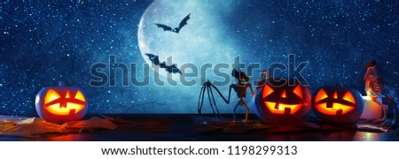 Halloween holiday concept banner. Pumpkins over wooden table at night scary, haunted and misty forest #1198299313
