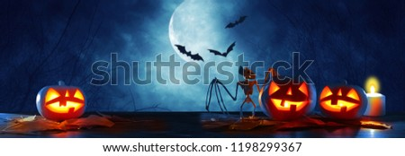 Halloween holiday concept banner. Pumpkins over wooden table at night scary, haunted and misty forest - Shutterstock ID 1198299367