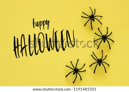 Halloween holiday concept. Black spiders over yellow background. Top view, flat lay #1191481501