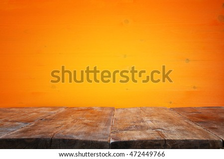 Halloween holiday concept. Empty rustic table in front of orange wooden background. Ready for product display montage