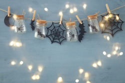 Halloween holiday concept. Mason jars with spiders, baths and wooden decorations.