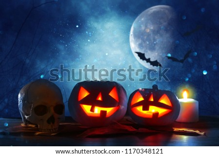 Halloween holiday concept. Pumpkins over wooden table at night scary, haunted and misty forest #1170348121
