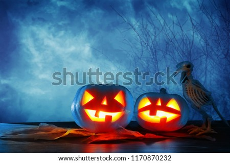 Halloween holiday concept. Pumpkins over wooden table at night scary, haunted and misty forest #1170870232